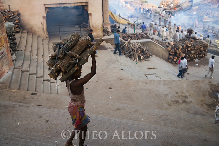 Man carrying fire wood down stairs to burning ghat where people are being cremated; Varanasi has been a cultural and religious center in northern India for several thousand years, Varanasi, Uttar Pradesh, India