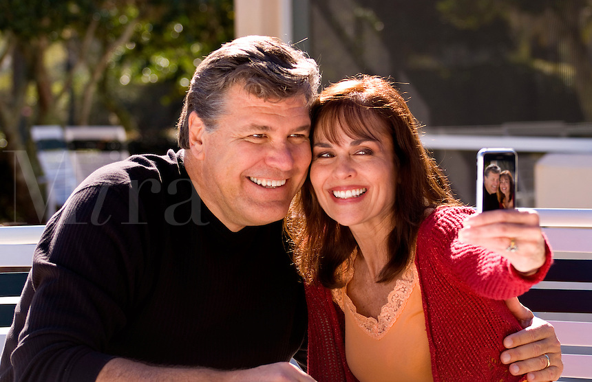 Couple in 50s at home taking pictures with I Phone cell phone laughing and relaxing in patio married