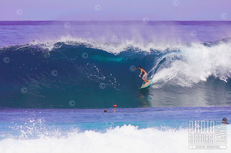 A longboarder pulls into the barelling section of the wave at Off the Wall.