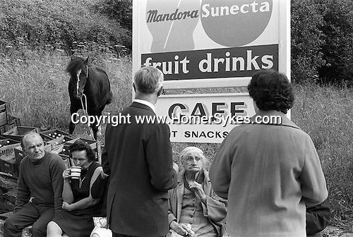 Family outing with Granny, who doesn't have her false teeth in. They have stopped for a cup of tea. Sitting on the wall of the car park for the cafe. Derbyshire Peak district. England 1970