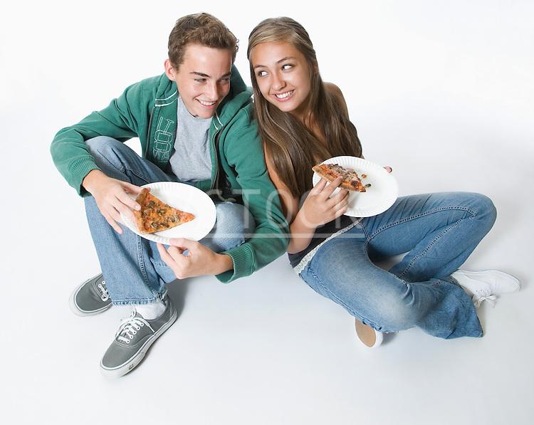 Teenage couple eating pizza