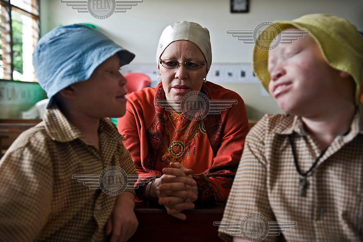 Madame Al-Shaymaa J. Kwegyir visits a boarding school in Dar es Salaam where two girls with albinism are being educated: 9 year old Tindi (left) and her 11 year old sister Bibiana. After their father died they were attacked by people from their village who took two fingers and cut off Bibiana's leg. Kwegyir found the girls at a hospital, adopted them and took their case to court. Kwegyir is Tanzania's first albino Member of Parliament. The nomination of an albino MP is a first step in the fight against the widespread belief that albinism is the result of a curse. Discrimination against albinos is a serious problem throughout sub-Saharan Africa, but recently in Tanzania albinos have been killed and mutilated, victims of a growing criminal trade in albino body parts fuelled by superstition and greed. Limbs, skin, hair, genitals and blood are believed by witch doctors to bring good luck, and are sold to clients for large sums of money, carrying with them the promise of instant wealth.