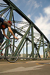 Low angle view of people biking across the Hawthorne Bridge into Downtown Portland, Oregon