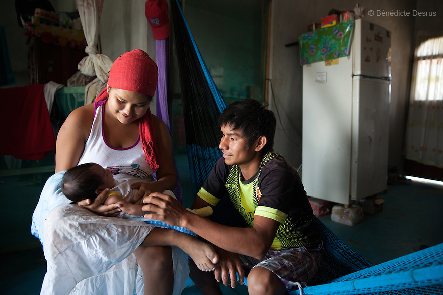 "Luz Betsaida Orozco Pineda and José Manuel Regalado López, her 17-year-old husband, with their new born baby at their home in Juchitán, Mexico on February 17, 2016. José Manuel gets up at 3 am to collect scrap and fish; their home is around 15 minutes from the beach. He speaks little Spanish. Now 14, Luz became pregnant when she was 13 after being ""stolen"" according to the Zapotec Indigenous tradition. Considered a traditional kind of marriage – Luz is too young to wed legally – the custom dictates that the couple go to the young man's house and announce their plans to marry. While the family waits, the couple go to a room together; he emerges later with a blood-stained handkerchief to prove his bride's virginity. Luz, who started going out with the father of her baby when she was 10, lives with her in-laws in the 6 de noviembre neighbourhood on the outskirts of Juchitán in the southern Mexican state of Oaxaca. Her baby was born on January 13, 2016. Despite following tradition, she speaks little Zapotec – the language of her husband and his family – she follows tradition, wearing a headscarf to protect her health as she is still observing the 40-days quarantine period after giving birth, during which she stays in the house. While Mexico has outlawed marriage under the age of 18, many young girls become unofficial wives and mothers much earlier. In Juchitán, teenage pregnancy is expected, even prized. Mexico ranks first in teenage pregnancies among the member countries of the Organization for Economic Co-operation and Development (OECD). Photo by Bénédicte Desrus"