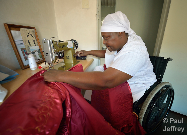 Jennifer Mhlanga suffered a spinal injury in a bus accident, and today uses a wheelchair to get around her home and neighborhood in Harare, Zimbabwe. Here she sews in her house, using her hand to activate the foot switch. Mhlanga supports herself by sewing items she exports to South Africa. Her wheelchair, which was carefully fitted to her individual needs, was provided by the Jairos Jiri Association with support from CBM-US.