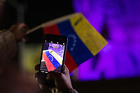 MEXICALI,  MEXICO - January 24. A person takes a picture with her phone of a Venezuelan flag a public demonstration supporting Juan Guaido on January 24, 2018 in Mexicali, Mexico. Donald Trump has promptly recognized formerly-unknown Juan Guaigó as interim president of Venezuela. Sec. of State Mike Pompeo announced that the US is ready to provide more than $20,000,000 in humanitarian aid to the people of Venezuela. (Photo by Luis Boza/VIEWpress)