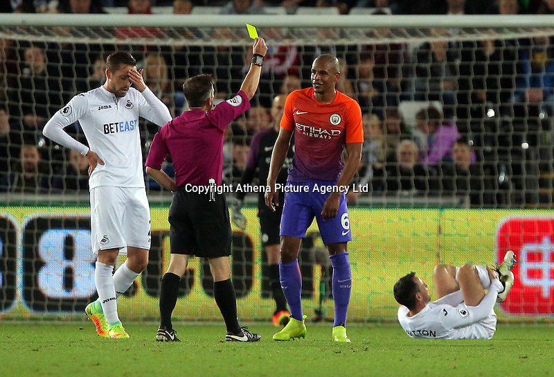 Fernando of Manchester City sees a yellow card by match referee Keith Stroud during the EFL Cup Third Round match between Swansea City and Manchester City at The Liberty Stadium in Swansea, Wales, UK. Wednesday 21 September.