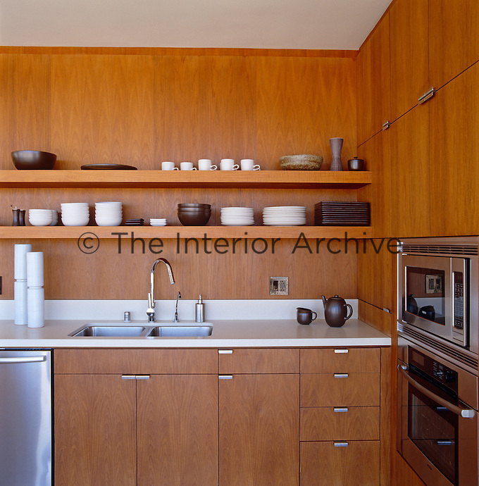 A teak panelled kitchen with a collection of Heath ceramic crockery on the open shelves