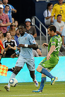 Kei Kamara (23) midfielder Sporting KC passes the ball past  Zach Scott (20) defender Seattle Sounders,.. Sporting Kansas City were defeated 1-2 by Seattle Sounders at LIVESTRONG Sporting Park, Kansas City, Kansas.