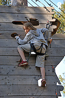 Girl (9) climbing over an outdoor wooden wall (Licence this image exclusively with Getty: http://www.gettyimages.com/detail/100408147 )