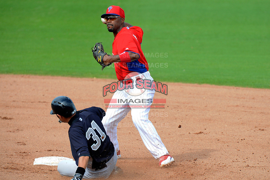 Philadelphia Phillies shortstop Jimmy Rollins looks to turn a double play as Ichiro Suzuki #31 slides in to break it up during a Spring Training game against the New York Yankees at Bright House Field on February 26, 2013 in Clearwater, Florida.  Philadelphia defeated New York 4-3.  (Mike Janes/Four Seam Images)