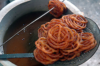 Hot Jalebis (sweets) are selling at a street food stall at Dalhousie area in Kolkata. Street food stalls are serving the office goers for decades. All kind of Indian foods are available on the street at an affordable price. They sale them openly. Street food stalls are another results of unempoloyment and over poppulation. They serve millions of people in India. Kolkata, West Bengal,  India  7/18/2007.  Arindam Mukherjee/Landov