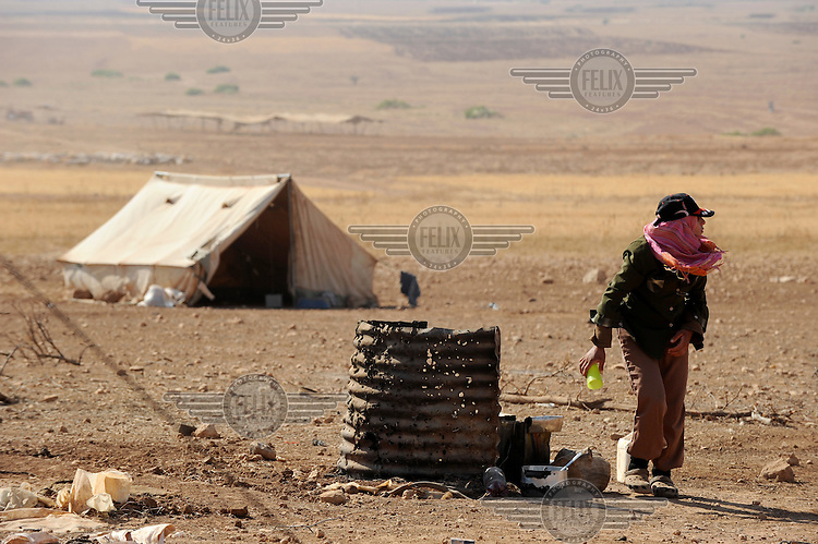 A girl walks past a makeshift oven at her family's encampment. Bedouin living in the Hadidiyeh area which lies close to the Israeli settlement of Ro'ee and in a declared military fire zone, are threatened with eviction orders issued by Israeli authorities.