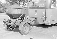 A car with a wood gas generator on a trailer.
