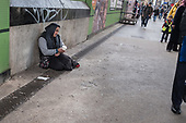 Woman begging in Whitechapel Market, London.