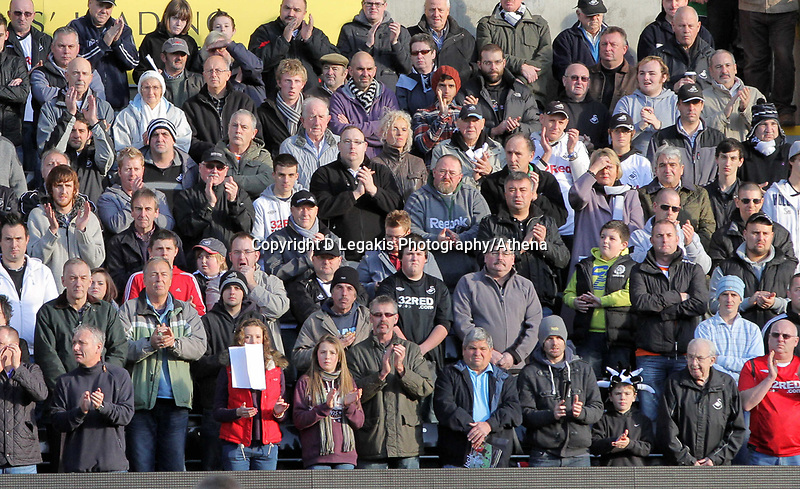 Pictured: Mixed feeling for Swansea supporters as some observe a minute's silence  and some applaud before kick off in memory of Wales football manager Gary Speed who has died. Saturday 27 November 2011<br /> Re: Premier League football Swansea City FC v Aston Villa at the Liberty Stadium, south Wales.