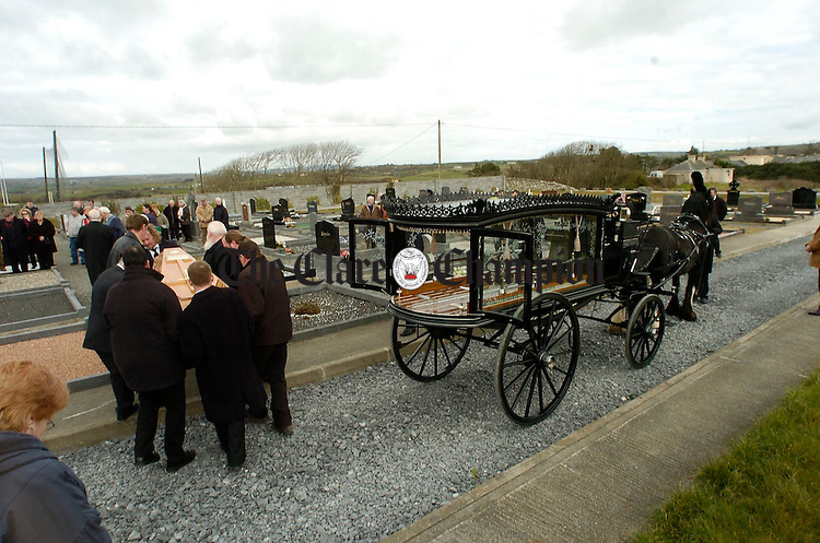 The remains of local man Michael Neylon are taken from the horse drawn hearse for burial in his final resting place at Ennistymon. Photograph by John Kelly.