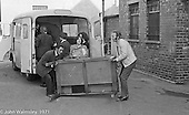 Bill Murphy, white jacket, lifting table.  Moving equipment and books into the building, Scotland Road Free School, Liverpool  1971.  Also known as the Scotland Road or Scottie Road Free School it was founded and run by two teachers, John Ord and Bill Murphy (if I've got these names wrong, please tell me!) who worked with truanting kids and provided somewhere to go and things to do.  They begged and borrowed an old building, desks, books and an old ambulance for trips.