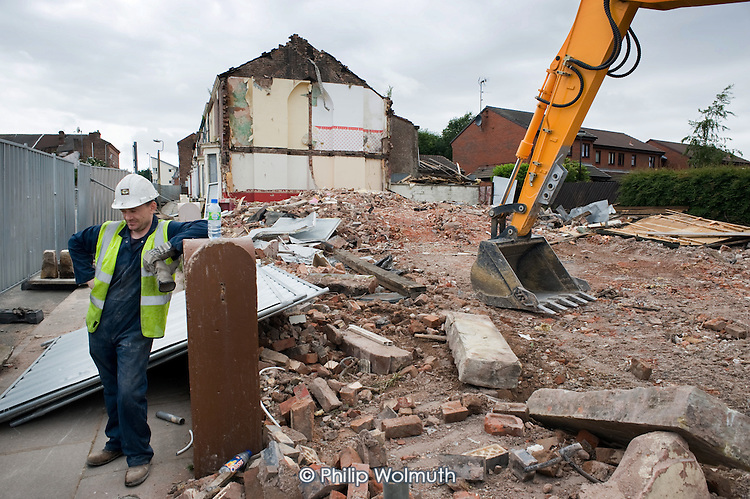 Building workers in a street of houses being demolished in Anfield, close to Liverpool football stadium, part of a programme by the Merseyside NewHeartlands partnership, financed by the Housing Market Renewal Fund, the government strategy aimed at tackling 'low demand'.  Some long-standing residents oppose the demolition of their homes.