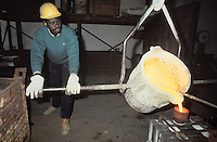 - African immigrant working in a foundry....- immigrato africano al lavoro in fonderia