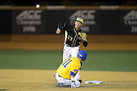 Wake Forest Demon Deacons shortstop Bruce Steel (17) attempts to turn a double play as Austin Niggebrugge (11) of the Delaware Blue Hens slides into second base at Wake Forest Baseball Park on February 13, 2015 in Winston-Salem, North Carolina.  The Demon Deacons defeated the Blue Hens 3-2.  (Brian Westerholt/Four Seam Images)