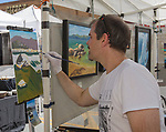 Lewis Kawecki paints in his booth during Art Fest on Sunday July1, 2018 in downtown Reno.