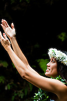 Beautiful Hawaiian woman wearing a haku and maile lei raises her hands in hula motion