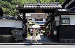 A woman walks past a cafe located in a building that was once a samurai residence in Shiomi Nawate district near Matsue Castle in Matsue City, Shimane Prefecture, Japan on 26 June 2011.  Photographer: Robert Gilhooly