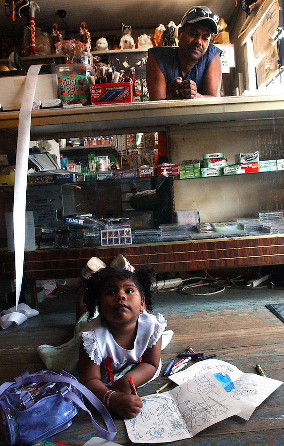 "Journal photo by Ted Richardson:  10/10/2004  Juan Roman watches his daughter Ariel Roman Gonzales, 2, as she takes a break from her coloring books on the floor of Roman's convience store, ""Costa Chica"", on Sprague St."