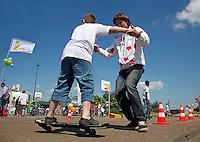 Buitenspeeldag in Amsterdam. Vrijwilliger helpt  een jongen met waveboarden