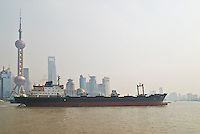 Empty freighter traveling up Huangpu river, Shanghai, China