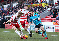 Lewis Coyle of Fleetwood Town runs past Craig Alcock of Doncaster Rovers ad Alfie Beestin of Doncaster Rovers during the Sky Bet League 1 match between Doncaster Rovers and Fleetwood Town at the Keepmoat Stadium, Doncaster, England on 17 February 2018. Photo by Leila Coker / PRiME Media Images.