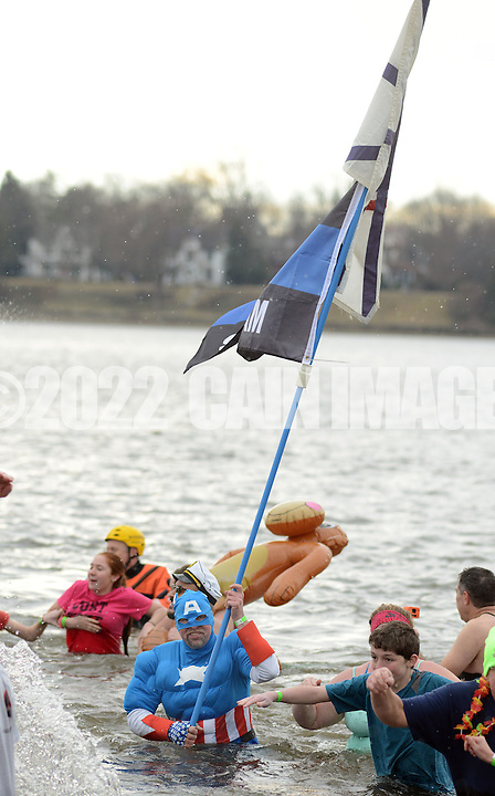 Mark Brasberger carries a flag as he braves the chilly Delaware River during the Polar Bear Plunge benefiting Special Olympics Saturday, January 27, 2017 at Neshaminy State Park in Bensalem, Pennsylvania. (Photo by William Thomas Cain)