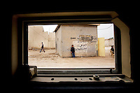 DIWANIYAH, IRAQ - MARCH 12: An Iraqi child leans against a graffiti covered wall and watches a passing American Army humvee on March 12, 2008 in Diwaniyah, Iraq. (Photo by Benjamin Lowy/Reportage by Getty Images)