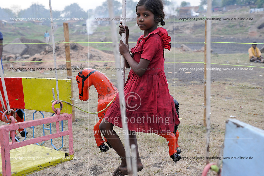 INDIA Jharkhand Dhanbad Jharia , girl Sonia in carousel , background smoke of burning underground coal seams, usually she works as coal picker / INDIEN Kohlerevier Dhanbad / Jharia , Maedchen Sonia 8 Jahre im Karussell auf einem Jahrmarkt vor brennenden Kohlefloezen, Sonia sammelt Kohle in Abraumhalden um Geld fuer die Familie zu verdienen