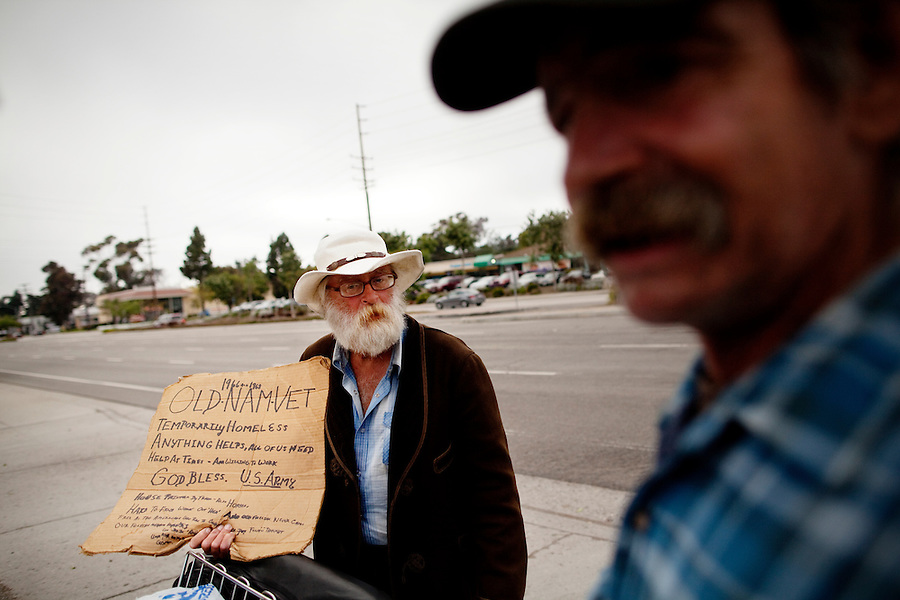 "Ventura, California, July 23, 2010 - Billy Joe McCall (left), a homeless veteran who was in the 82nd Airborne for two tours during the Vietnam War uses a sign to solicit donations from people on the edge of the Target parking lot while friend, Richard Allen Edwards (right) chats with him. Mr. McCall's life began to fall apart after his wife and child were killed by a drunk driver who was also high on PCP (phencyclidine piperidine). After learning the driver would only be charged with involuntary manslaughter, McCall says he paid for the man's bail and then shot him. ""I went into the bar where he hung out, laid down a .357 on the table and said go for it. He looked at me like I was crazy. But I had a .38 on my hip. He went for it and I shot him dead. I got almost three years for it."" After being released from prison, McCall's life began to unravel. He lost his painting business and says he worked for a stint with the mob in Florida. With a felony charge and a severe limp from a wound he received in Vietnam, jobs grew scarcer. He returned Texas for a period before coming to California to help take care of his ailing mother. Her medical bills and his lack of work left him with no other opportunities, but a life of the street. He says his VA pension will begin in September. ""That is going to get me off the streets once and for all."" ."