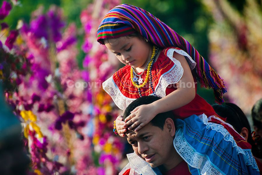"A Salvadoran man carries his daughter on his shoulders during the procession of the Flower & Palm Festival in Panchimalco, El Salvador, 8 May 2011. On the first Sunday of May, the small town of Panchimalco, lying close to San Salvador, celebrates its two patron saints with a spectacular festivity, known as ""Fiesta de las Flores y Palmas"". The origin of this event comes from pre-Columbian Maya culture and used to commemorate the start of the rainy season. Women strip the palm branches and skewer flower blooms on them to create large colorful decoration. In the afternoon procession, lead by a male dance group performing a religious dance-drama inspired by the Spanish Reconquest, large altars adorned with flowers are slowly carried by women, dressed in typical costumes, through the steep streets of the town."
