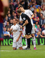 Pictured: Match referee C Pawson (C) sees to injured Jack Cork of Swansea<br />