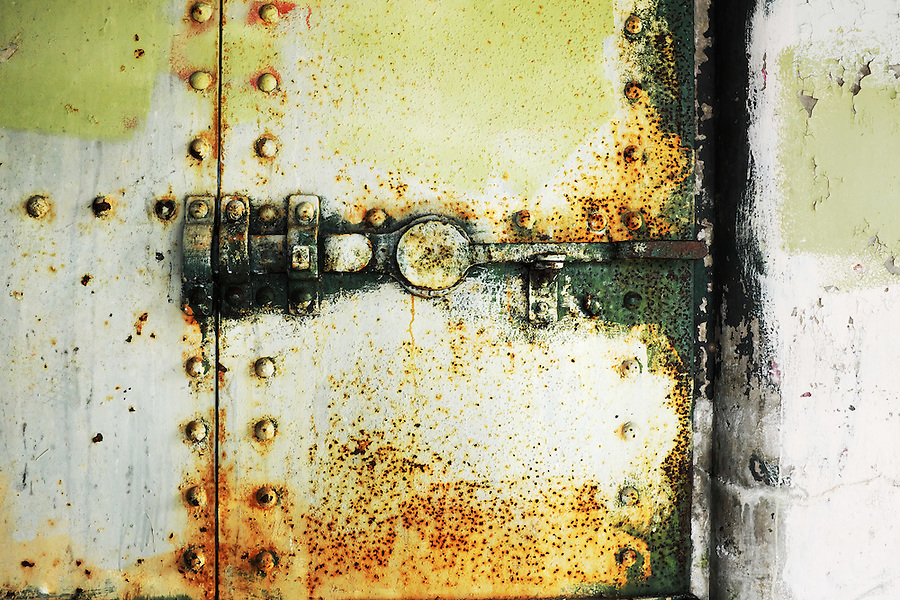 Rusty steel latch on closed yellow steel bunker tunnel door, Artillery Hill, Fort Worden State Park, Port Townsend, Washington, USA