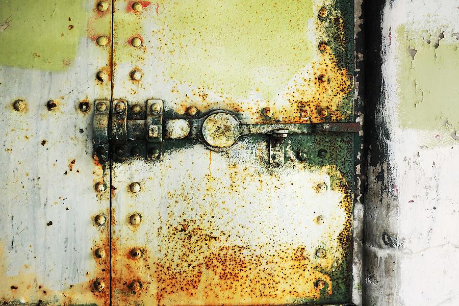 Rusty steel latch on closed yellow steel bunker tunnel door, Artillery Hill, Fort Worden State Park, Port Townsend, Washington, USA