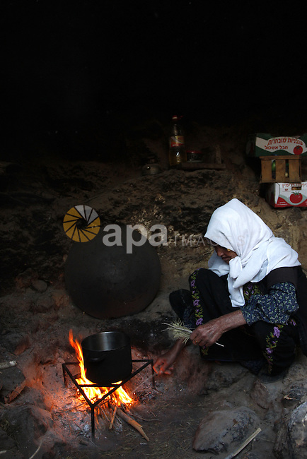 Palestinian woman cooks food inside a cave in a mountainous area outside the city of Hebron in the occupied West Bank on May 22, 2010. Photo by Mamoun Wazwaz