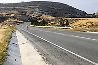 Stock image of lone cyclist on a hilly highway of Cyprus.