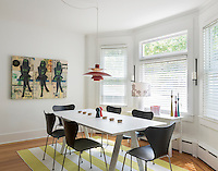 A modern, white dining room with a wood floor. The room is furnished with a white Thomas Eriksson table and black Arne Jacobsen butterfly back chairs standing on a yellow striped rug.