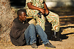 Arrested poacher being watched by anti-poaching scout, Kafue National Park, Zambia