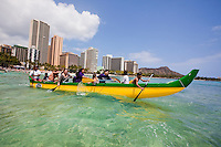 Kids enjoying a Hawaiian outrigger canoe ride off the shores of Waikiki