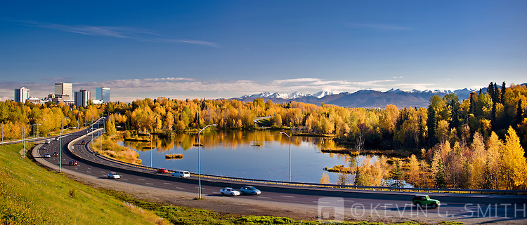 Traffic on Minnesota blvd. drives past Westchester Lagoon on the way into down town Anchorage, fall, Anchorage, Southcentral Alaska, USA.