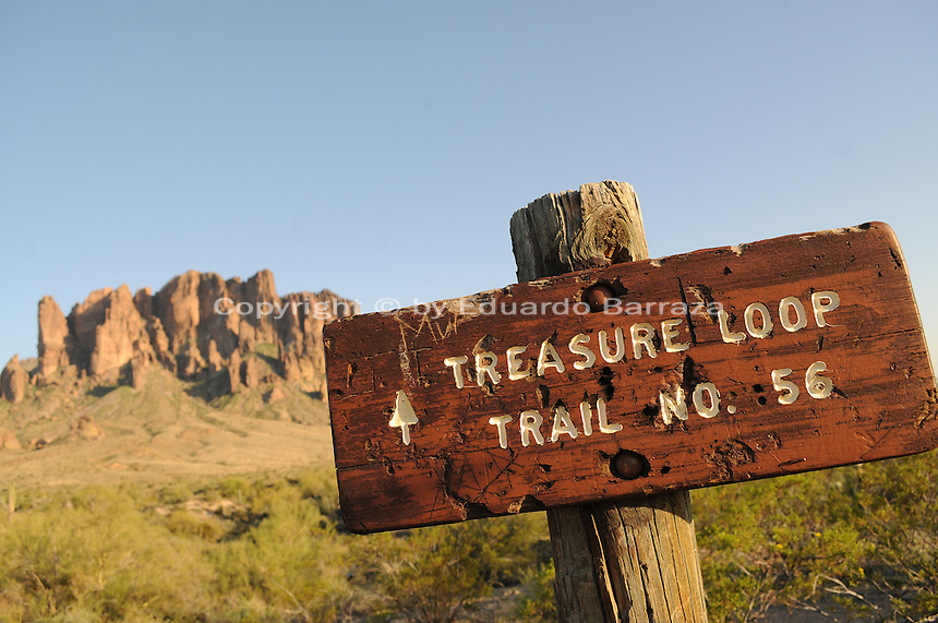 Apache Junction, Arizona. The Lost Dutchman State Park is located in the area of the Superstition Mountains in the Sonoran Desert, 40 miles east of Phoenix, Arizona. The park takes its name from a fabled lost gold mine. In this photograph, a sign points to hikers the entrance to the Treasure Loop Trail in the Lost Dutchman State Park. Superstition Mountain is the background. Photo by Eduardo Barraza © 2011