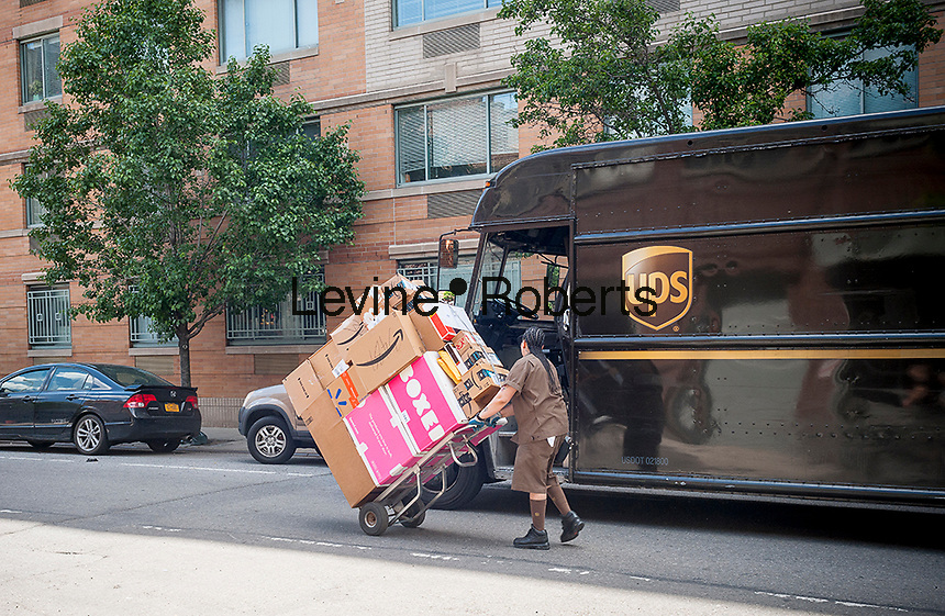A UPS worker, her handcart laden with packages, goes on her appointed rounds in Greenwich Village in New York on Thursday, June 1, 2017. (©Richard B. Levine)