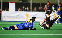 NZ's Steve Edwards goes flying after a collision with Baljit Singh Charun Singh during the international hockey match between the New Zealand Black Sticks and Malaysia at Fitzherbert Park, Palmerston North, New Zealand on Sunday, 9 August 2009. Photo: Dave Lintott / lintottphoto.co.nz