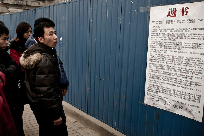 Bystanders are reading a billboard written by evicted  landlords who protest against the destruction of their houses in Beijing.<br /> <br /> Conflicts about housing destructions and relocation are very common in China and sometimes end in suicides of desperate inhabitants or attacks against those who resist by thugs employed by real eastate companies ...